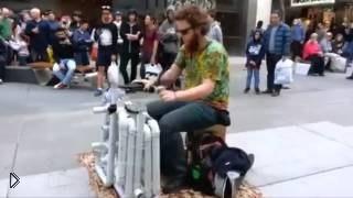 Смотреть онлайн Уличный музыкант развлекает прохожих игрой на трубах