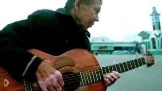 Смотреть онлайн Бездомный мужчина красиво играет на гитаре